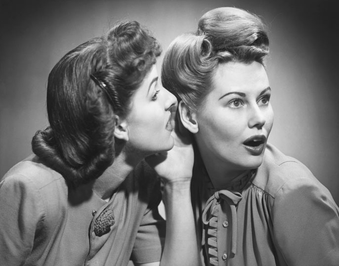 Two women in 50s hairstyles gossip in black and white photo