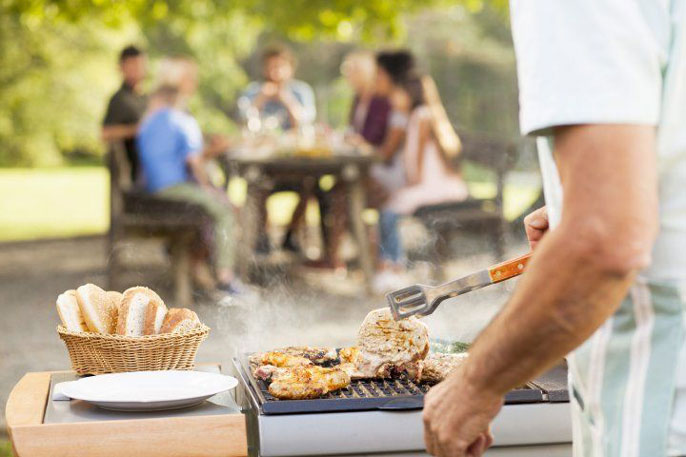 Chicken cooking on a grill with people in the background