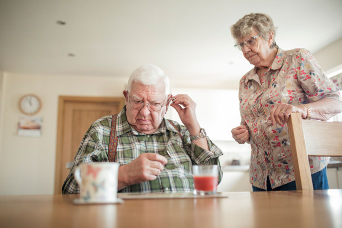 Hearing aid adjusted by senior man with senior woman nearby