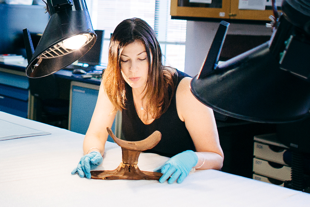 An archaeology grad student examines a wooden head rest artifact