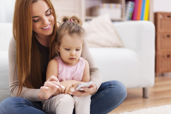 Mom and toddler looking at a cell phone
