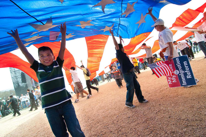 A child and several others under a large American flag