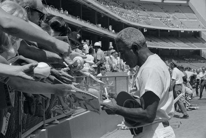 Jackie Robinson signing autographs at a game