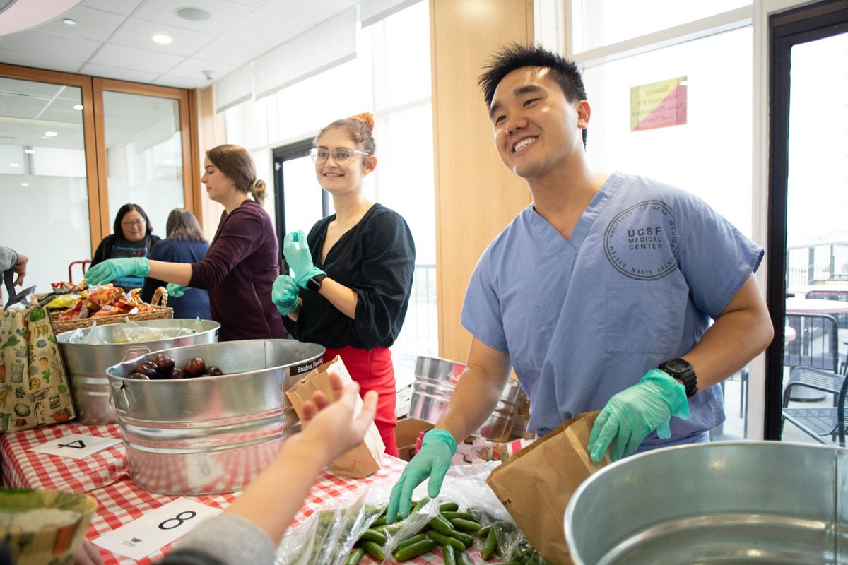 Jerry Liu at a volunteer event handing out foot in medical scrubs