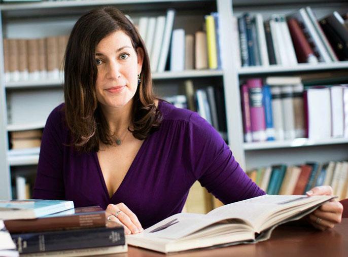 Kara Cooney at a desk with an open book