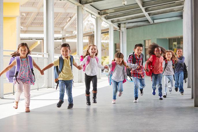 Kids run through an outdoor hallway