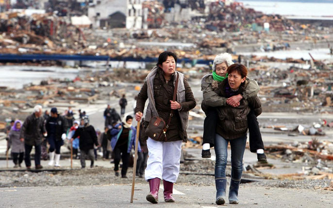 Two women walking, one carrying another, older woman