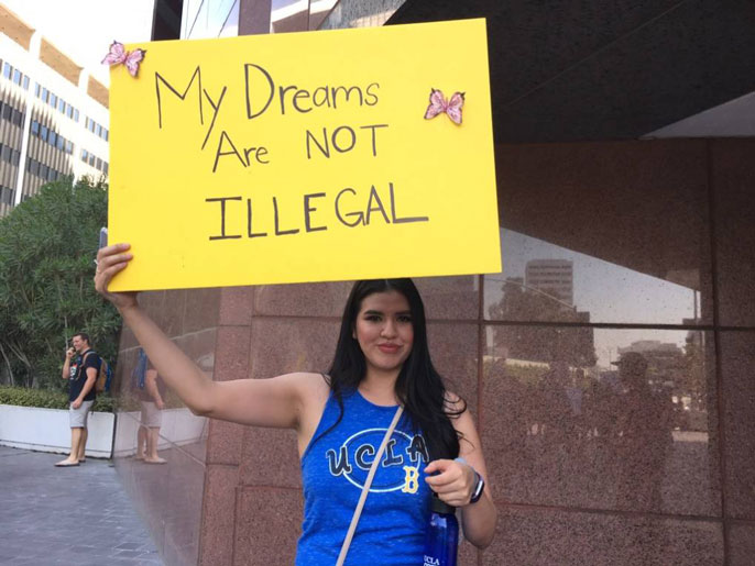 Woman holding a sign that says my dreams are not illegal