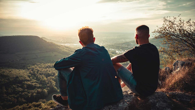 Two men stare down into a sunlit valley