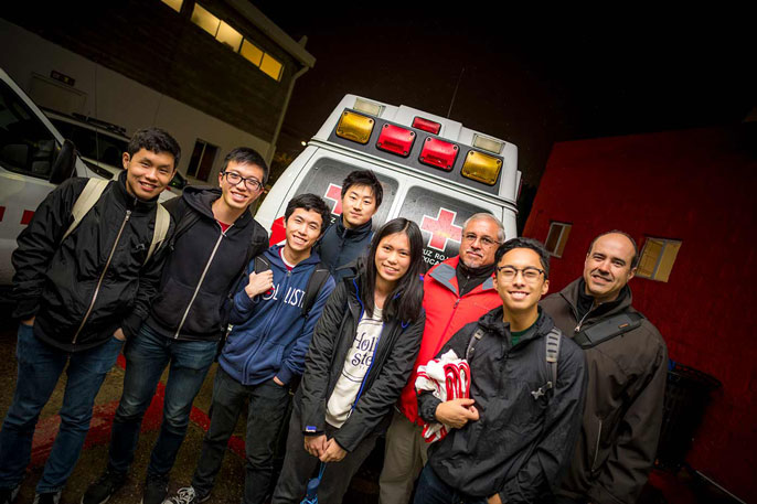 Students stand in front of an ambulance
