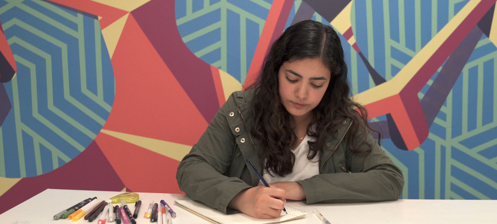 Frida writes in her notebook in front of a colorful wall