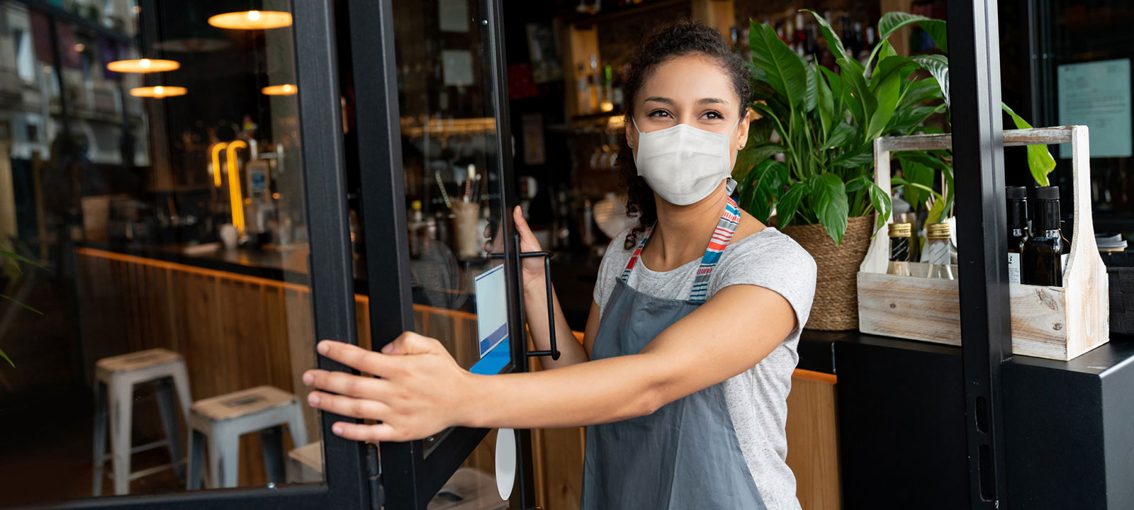 Woman wearing mask opens a cafe door