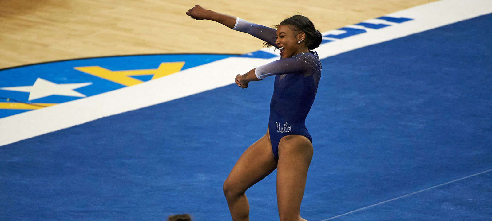 Nia Dennis smiling and pumping her fist while on the floor