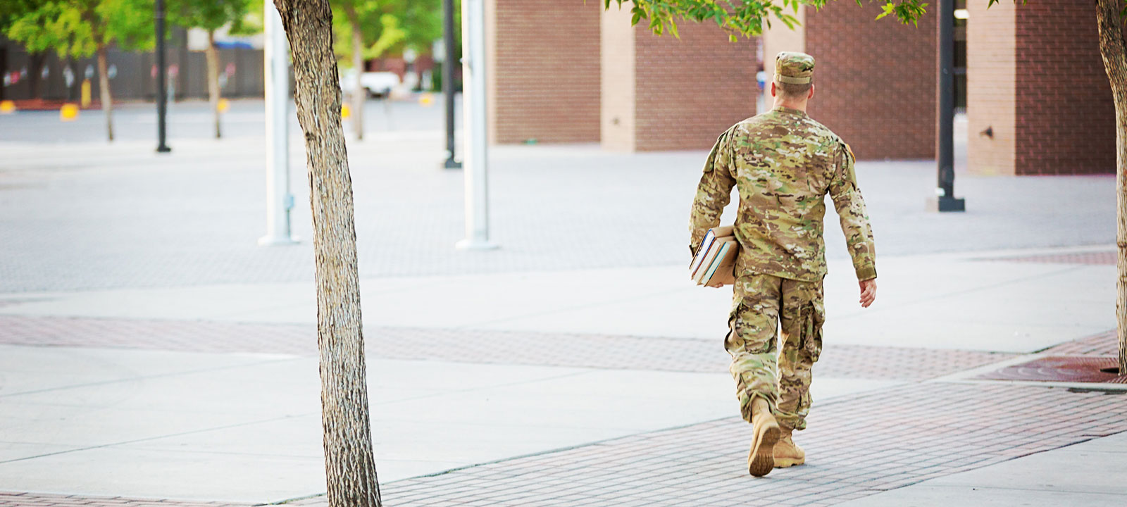 Soldier walks across a campus holding books