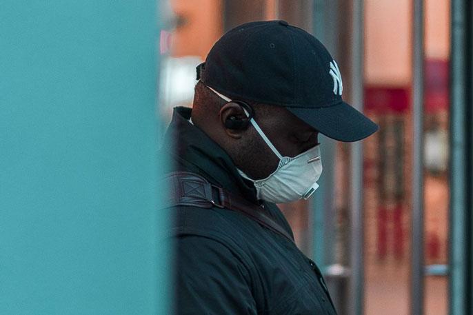 Black man wearing respirator mask outside