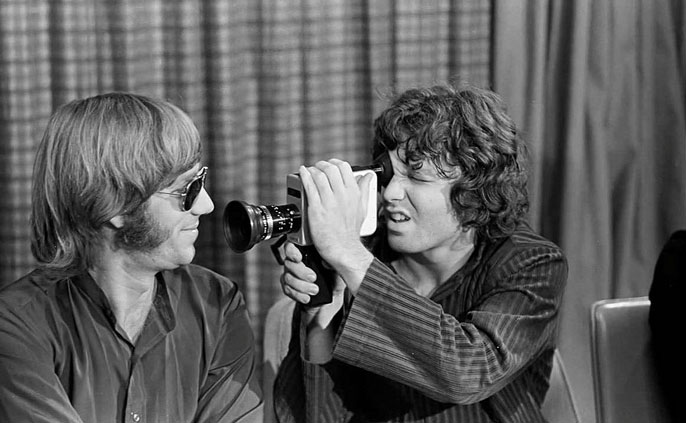 Jim Morrison holding a film camera up to Ray Manzarek