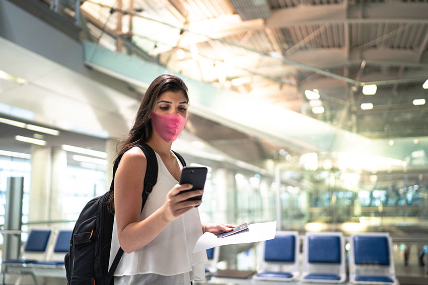 Woman at airport, checking her cell phone