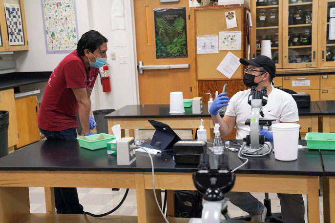 UC Davis students, masked, communicating in a lab
