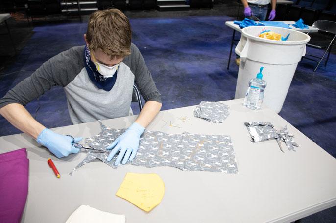 Young man sewing masks