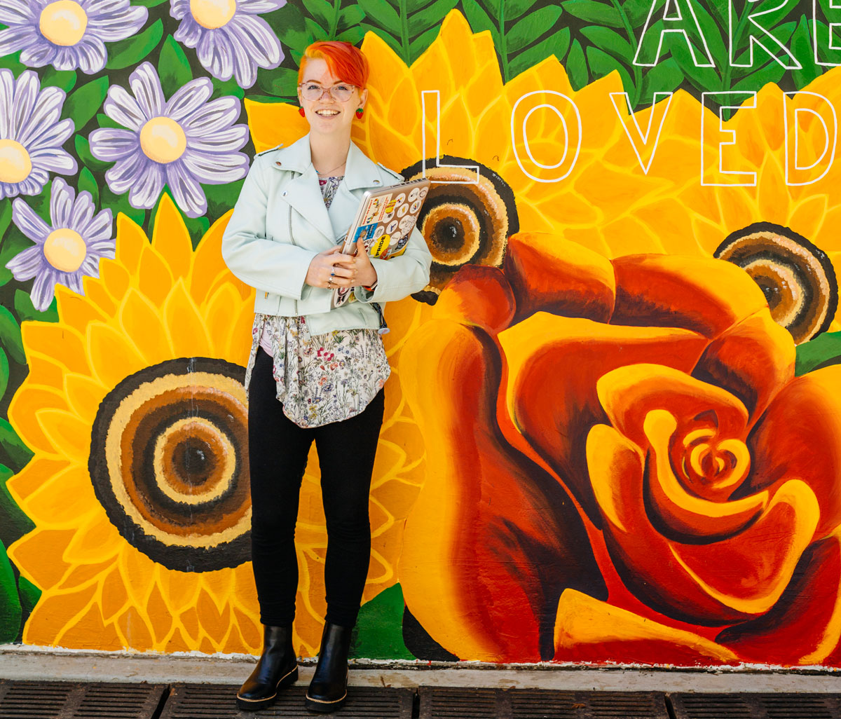 Female student stands in front of colorful red yellow and orange mural