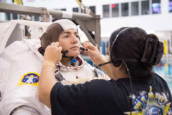 Meir in astronaut gear getting headset put on