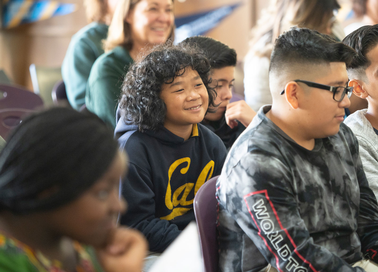 A middle school student listens to a college talk wearing a Cal sweatshirt