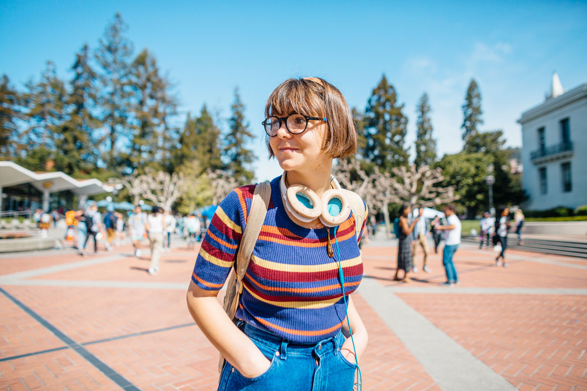 Female student in sweater looks around Sproul Plaza