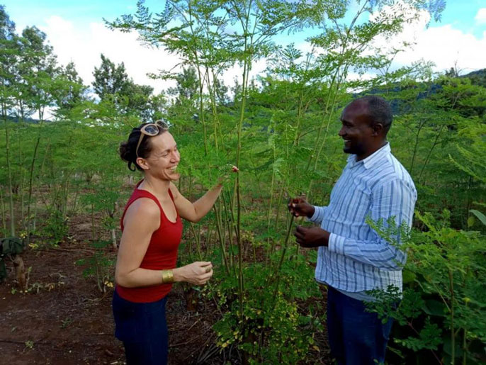 Carrie Waterman in front of moringa with Collins Mwenda