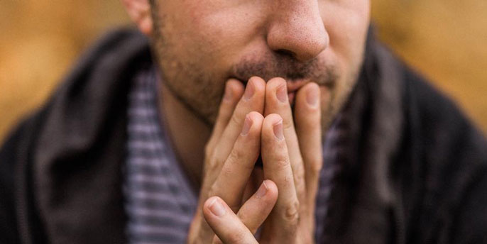 Man with hands over his mouth
