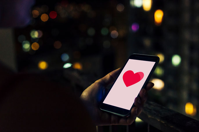 A phone with a heart on it at night