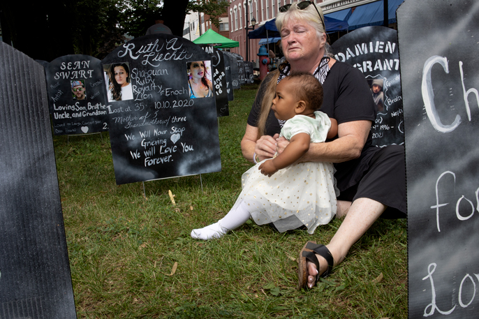 A woman holds a young child near an opiate memorial