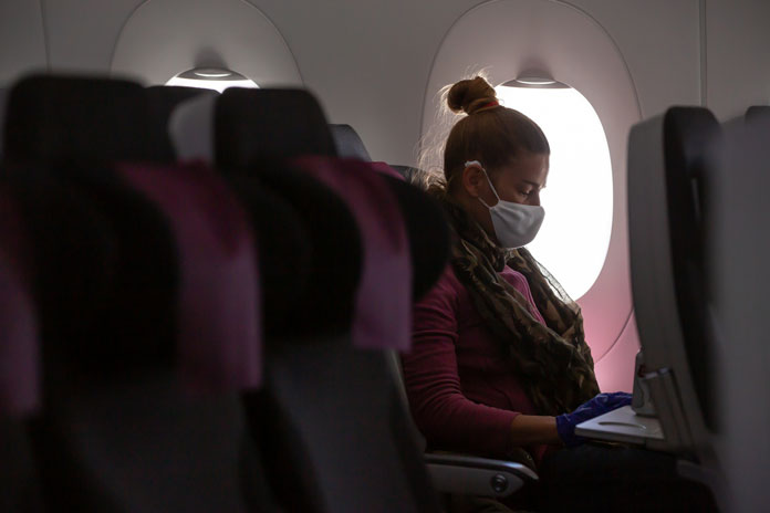 Woman on a plane wearing a mask alone in her row