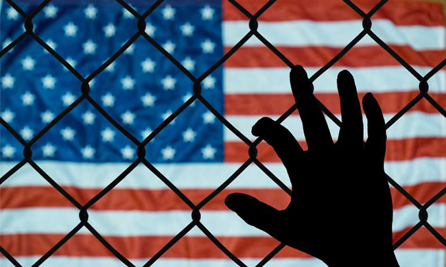 Hand on fence in front of an American flag