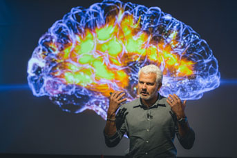 Man in front of a large brain image