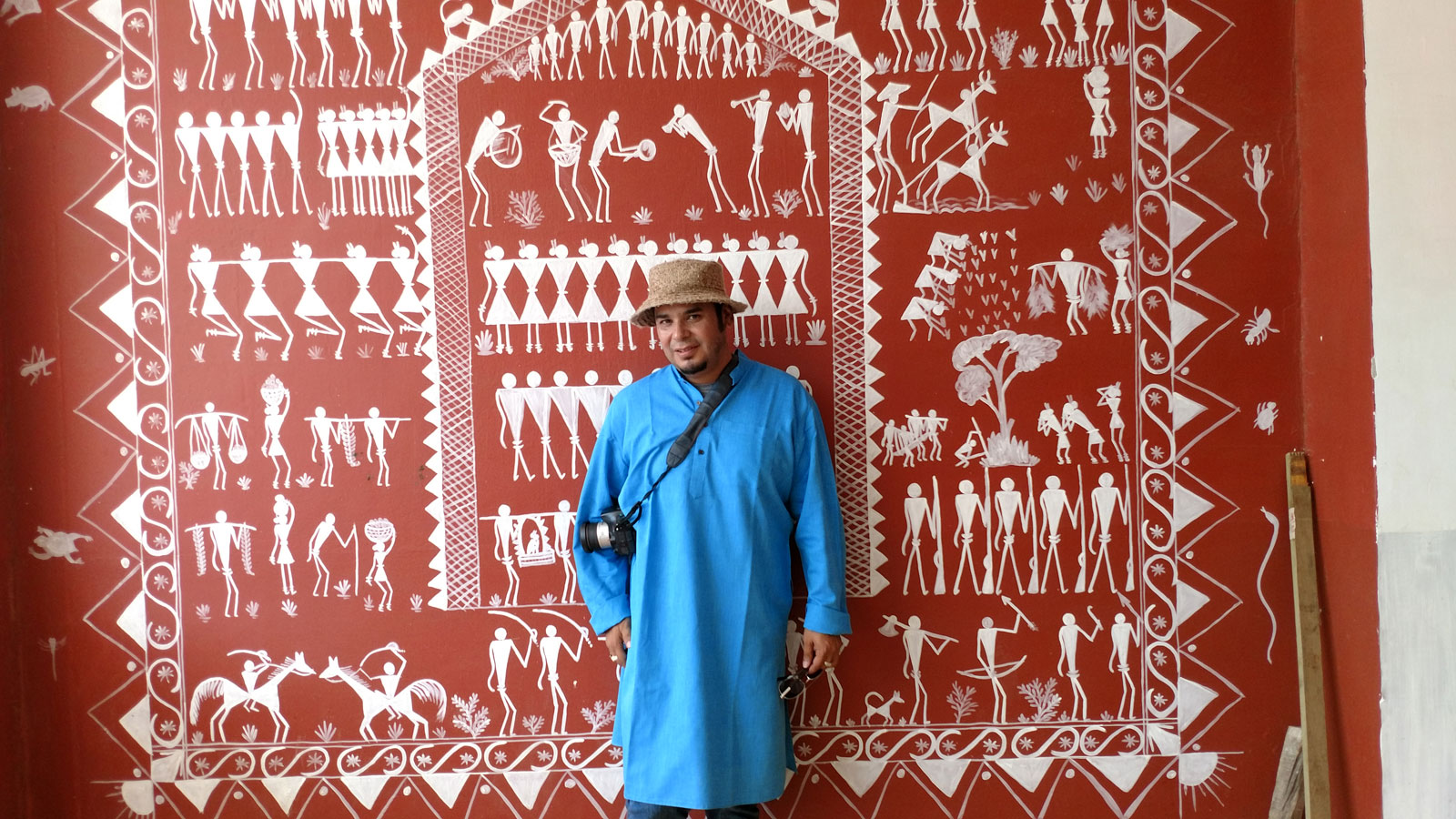 Ray Gutierrez stands in front of a mural of tribal symbols at Centurion University