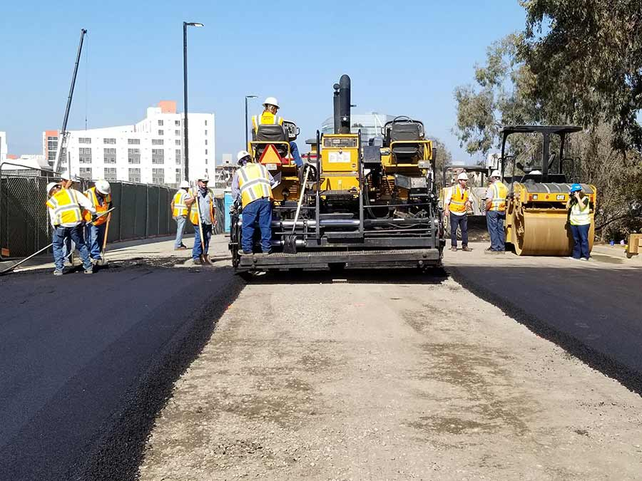 A work crew paves the road with material made of recycled plastic