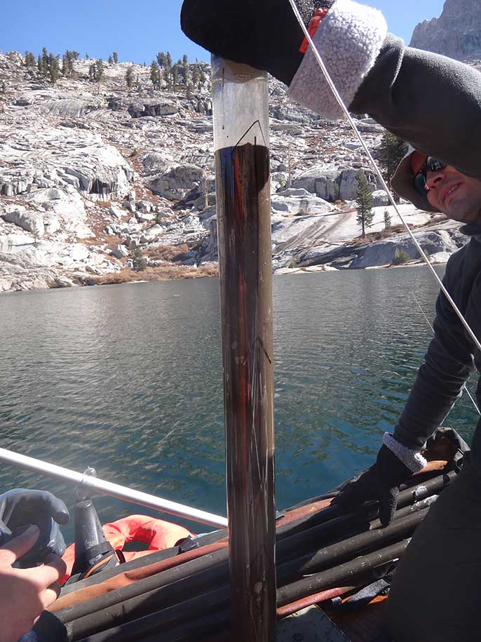 Peter Homyak collects lake sediment core
