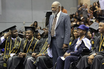 Roy Overstreet standing at UC Riverside graduation ceremony among crown
