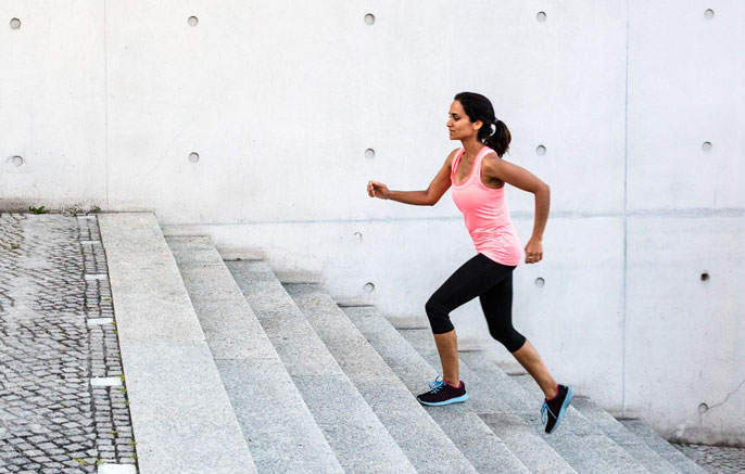 Woman jogging up grey steps outdoors