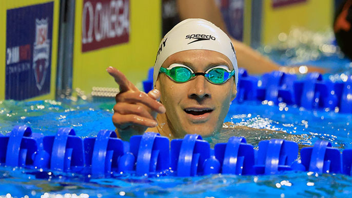 Ryan Murphy pointing from the pool in cap and googles just after a race
