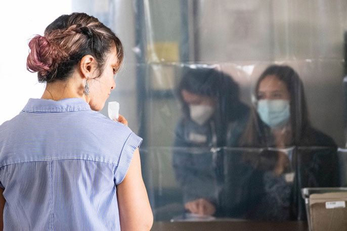 Woman staring through transparent plastic at people wearing PPE