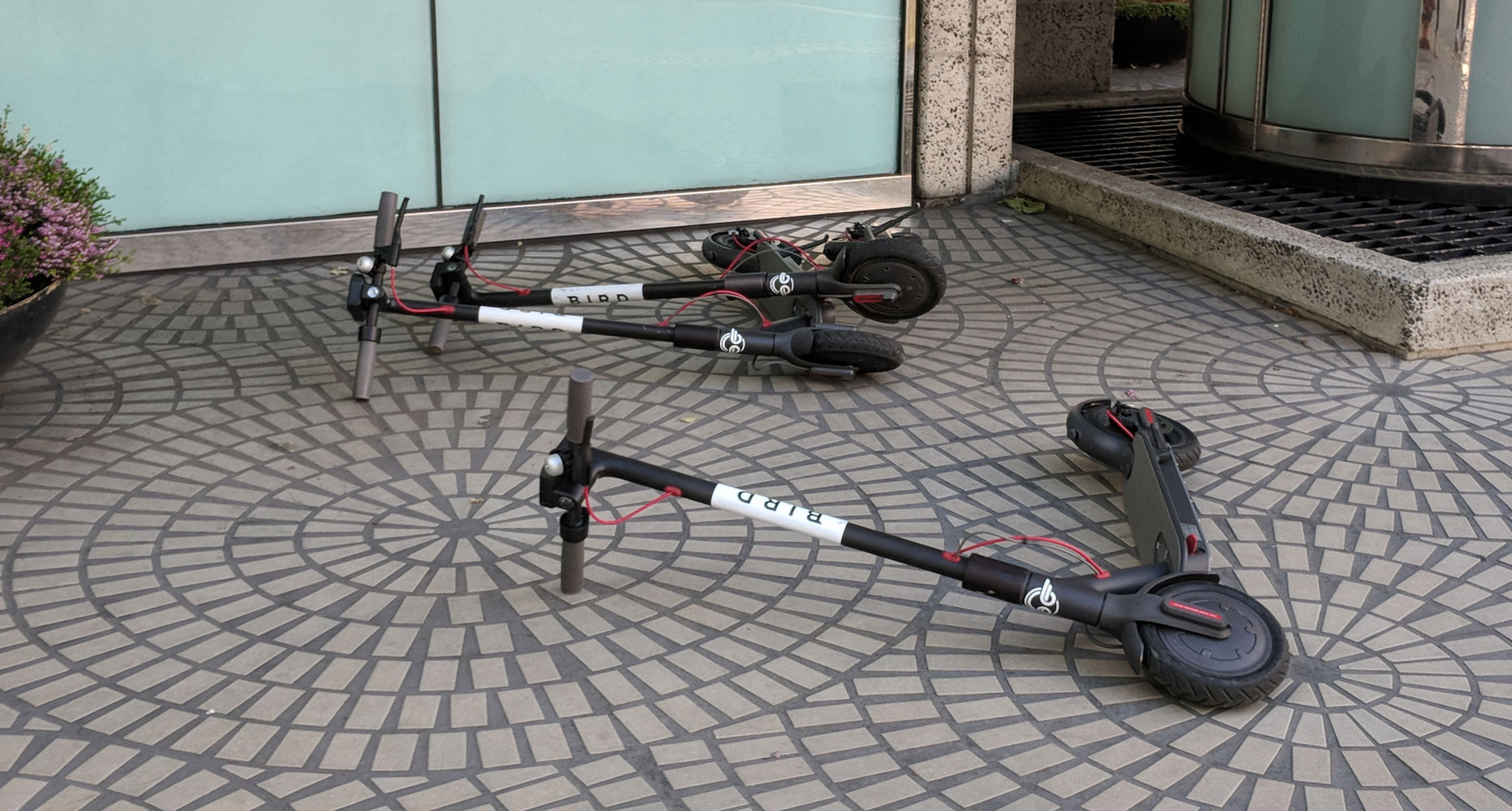 three scooters lying in the sidewalk