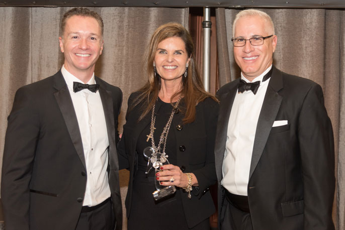 Maria Shriver at a gala with two men