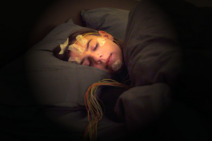 Woman sleeping with sensors on her head