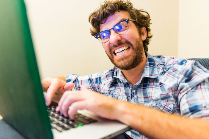 Outraged man typing on computer