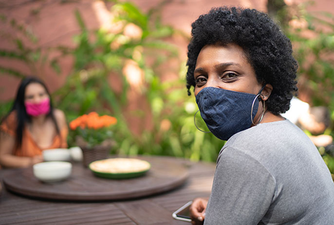 Black woman in mask looks at camera while socializing with friend outside