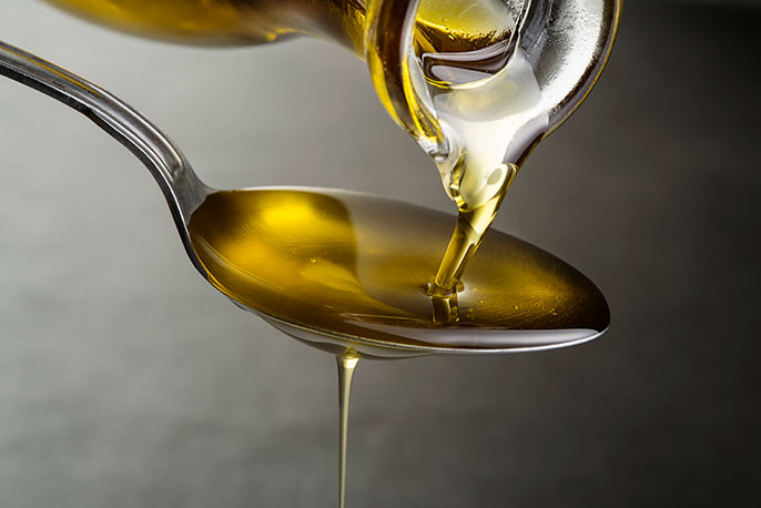 Soybean oil flowing into a spoon