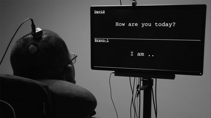 A man looks at a screen where his words appear while wearing a device on his head