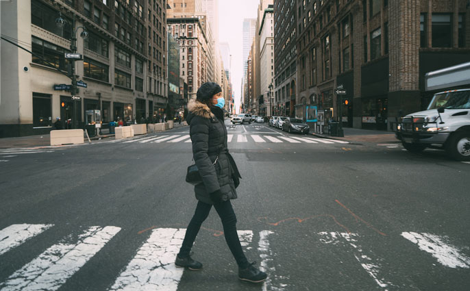 Woman walks down empty city street wearing a mask