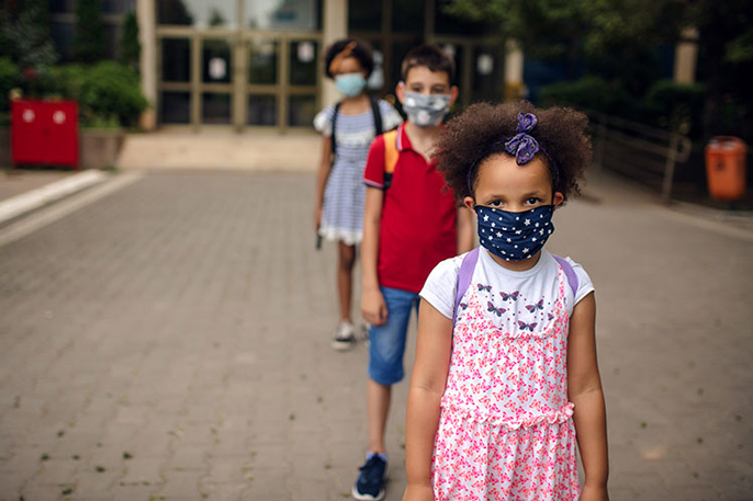 A line of young masked elementary school students